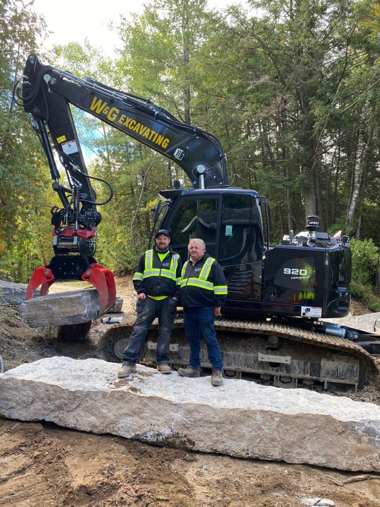Arthur and Waldemar Mikolajczyk standing in front of their Liebherr 920 compact excavator