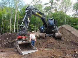 Waldemar Mikolajczyk posing beside the bucket of the Liebherr 920 compact excavator