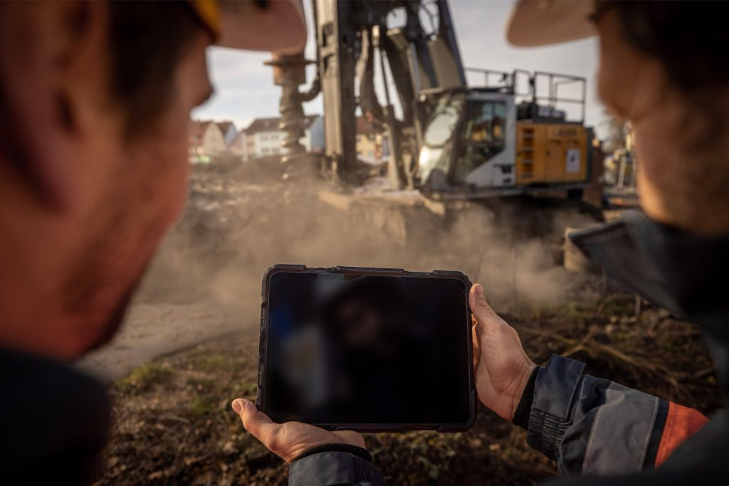 Two workers look at a tablet, where Liebherr shows machine data. In the background is a Liebherr drill rig.