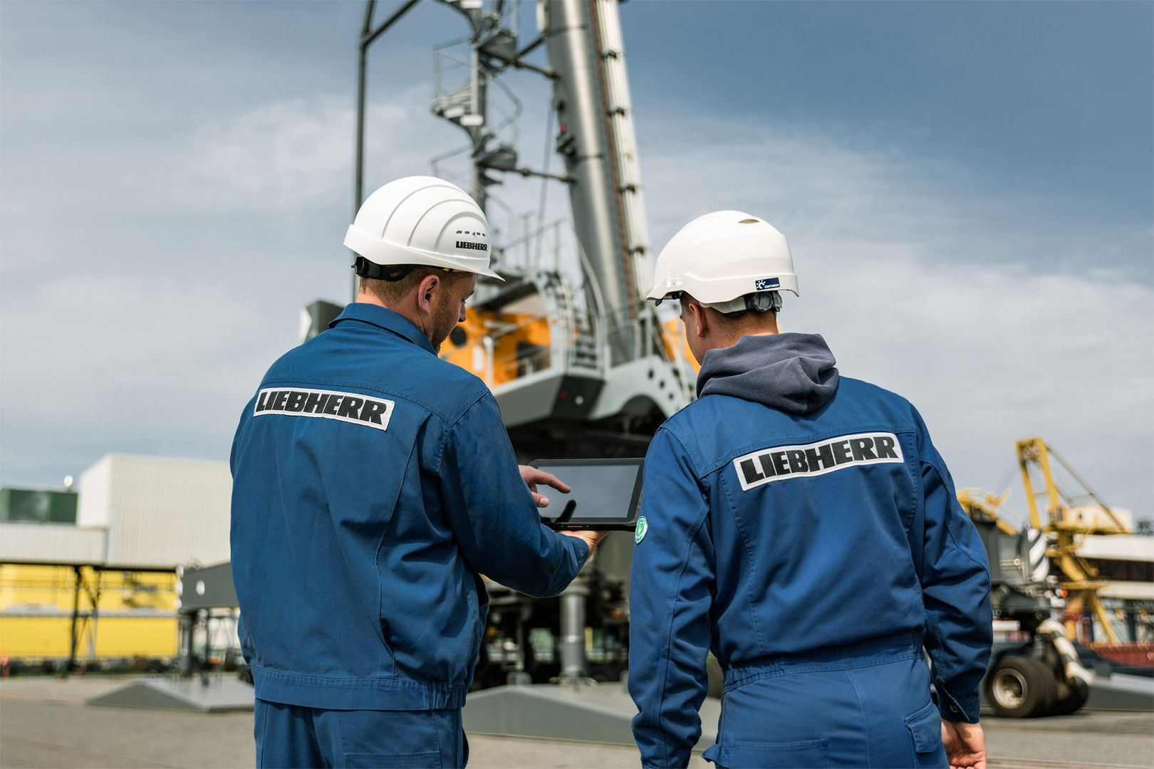 Liebherr employees, who are on a job site, examine data on a tablet using XpertAssist.