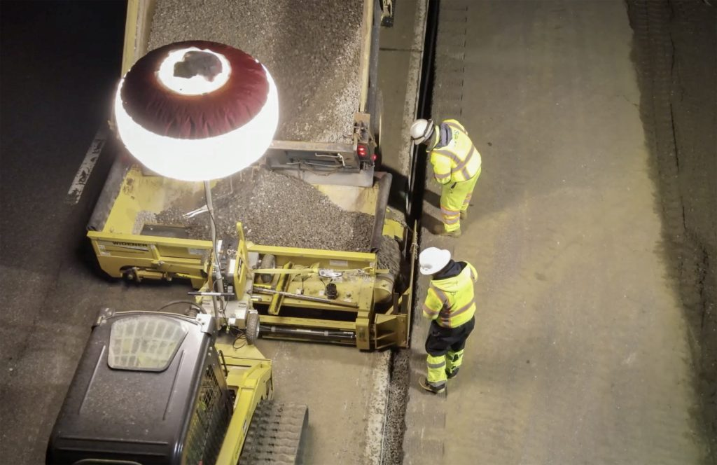 Road Widener's FH attachment spreading gravel at night, with the help of an industrial-sized light attached to the compact loader