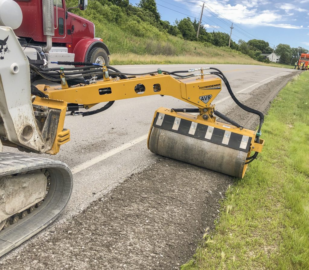 Road Widener's Offset Vibratory Roller in use, compacting a gravel extension to a paved road