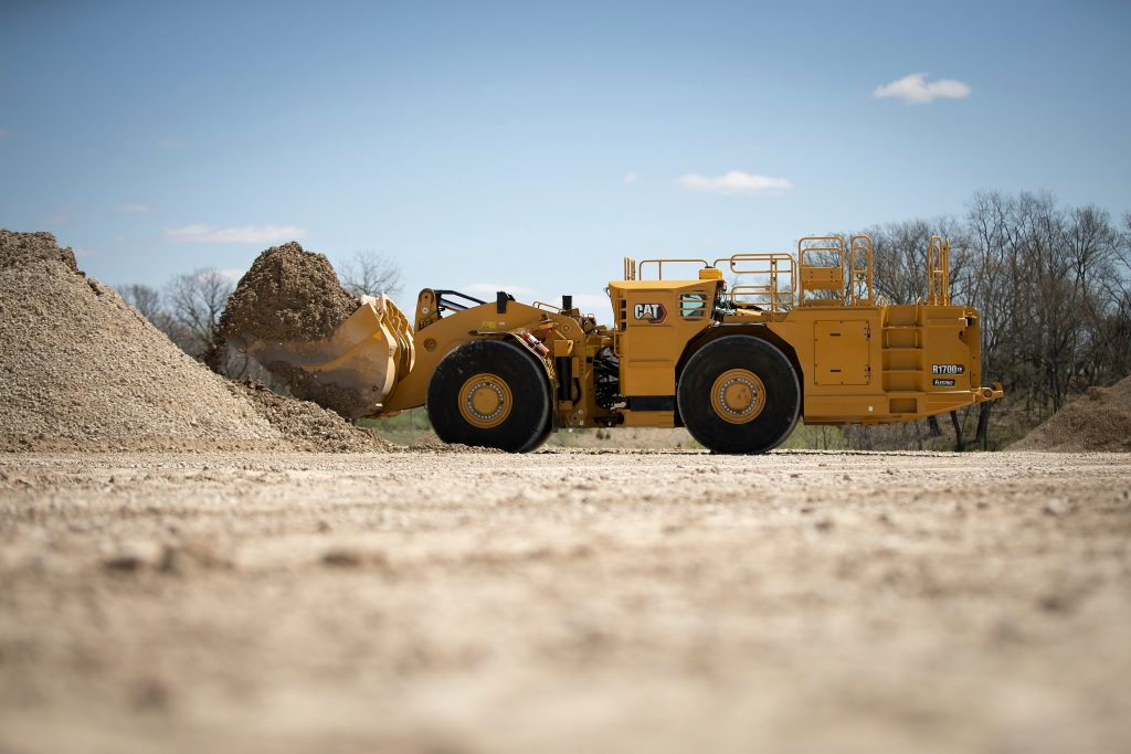 The R1700 XE picks up a bucket-full of material.