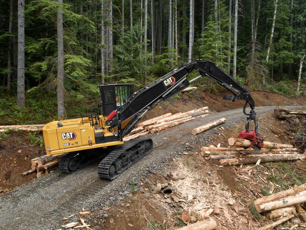 A CAT 568 Forest Machine picks up a log beside a roadway.