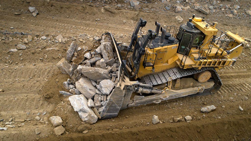 CAT D11 XE pushing large rock.