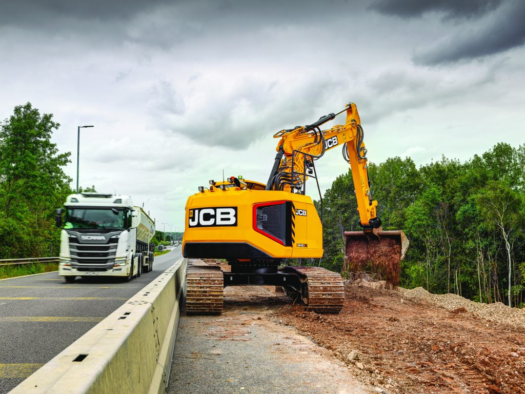 JCB 245XR works roadside, showing off its reduced tails swing by working right up against a barrier.