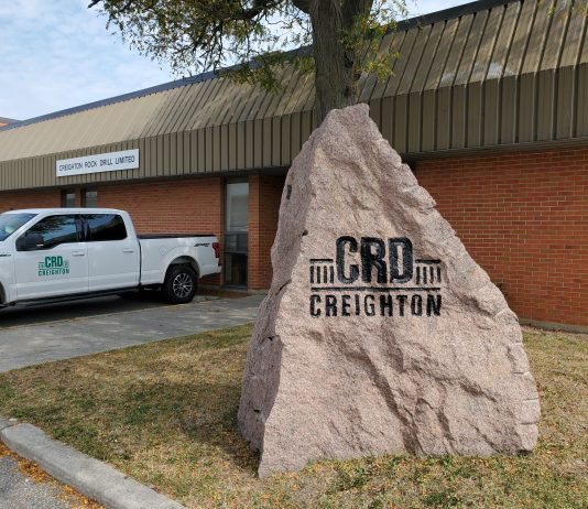 The Creighton Rock Drill Ltd. logo on a large piece of granite outside its headquarters.