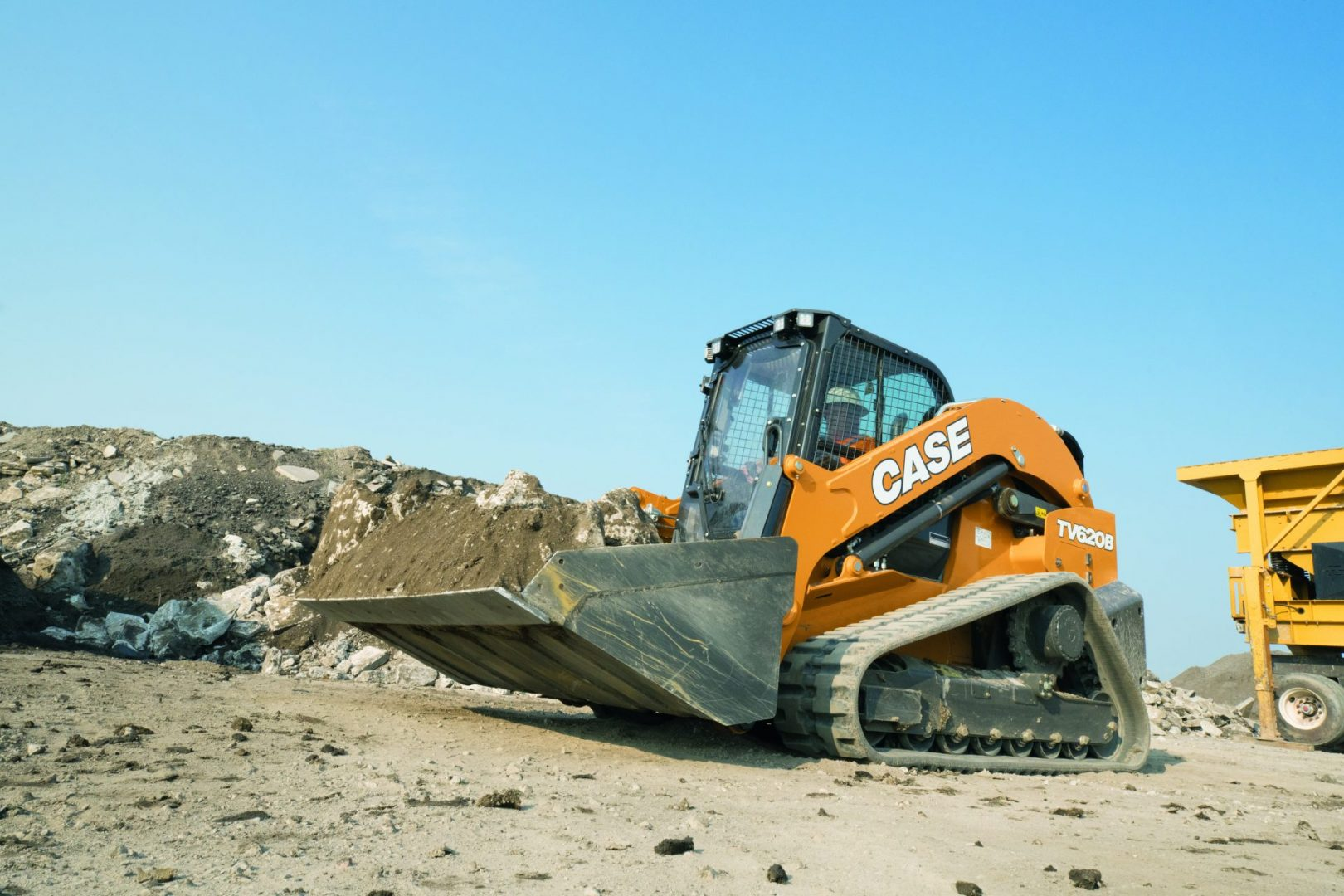 The CASE TV620B on-site with a bucket-full of material.