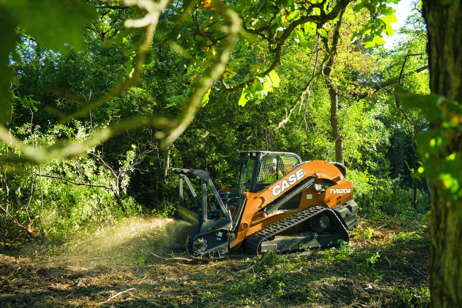 The CASE TV620B in a forest using a mulching attachment.
