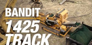 Screenshot from product video, showing the Model 1425 Track being fed by an excavator and its out-feed filling a trailer.