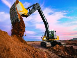 John Deere excavator dumps clay from its bucket, an excavator that is available through Fernandez's dealers.