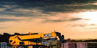 JCB rotating telehandler on-site, lifting pallets.